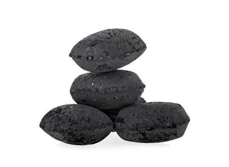 Heap of coal briquette for BBQ isolated on white background