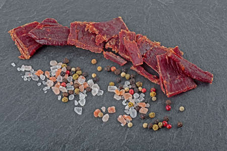 Beef jerky and spice on black stone table. Top view.  Stock fotó