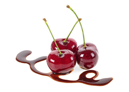 Three cherries in chocolate on a white background