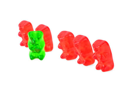 Green jelly bear with other red jelly bears isolated on a white background Banco de Imagens