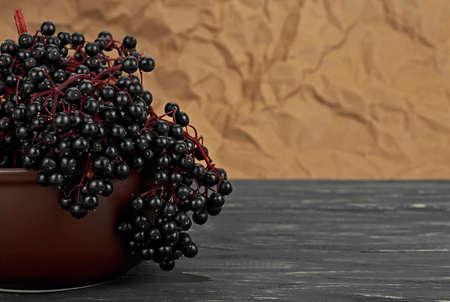 Berries of Elder Fruit in clay bowl, on wooden desk. Healing berries of ripe black elderberry.
