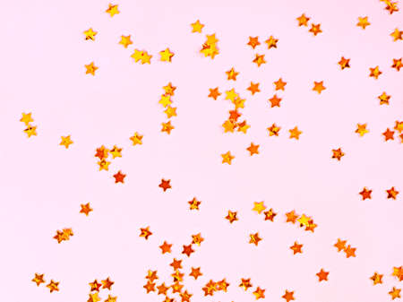 Pink background with golden stars, copy space. Golden stars confetti on pastel background.