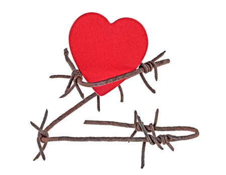 Rusty barbed wire wound around a wooden red heart isolated on white background, closeup.