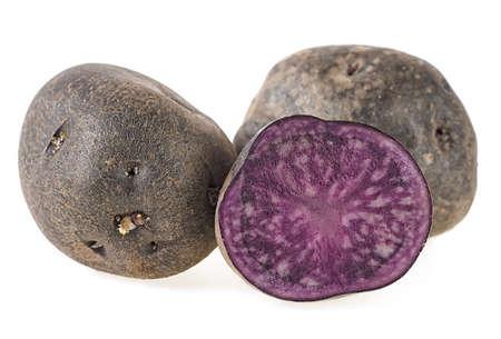 Fresh vitelotte potatoes isolated on a white background. Vitolette noir or purple potato.