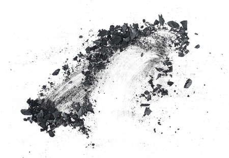 Black dust powder of charcoal on a white background, top view. Charcoal dust with fragments.