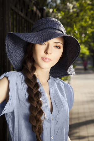 Portrait of attractive young girl in hat in the park photo