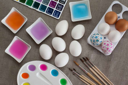 Colored water, watercolors, palette and brushes for decoration Easter eggs photo