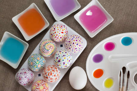 Colored water, watercolors, palette, brushes and painted Easter eggs photo
