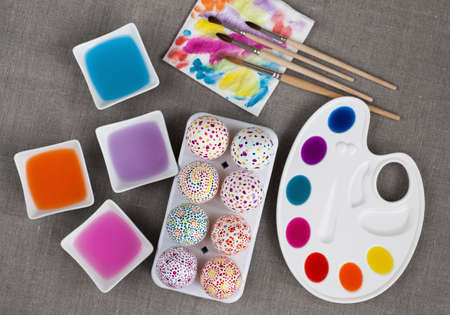 Colorful painted Easter eggs, colored water, palette and paintbrushes photo