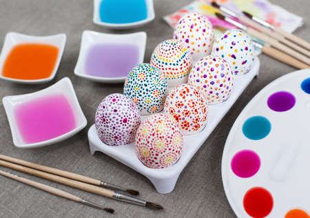 Colorful painted Easter eggs, colored water, watercolors and paintbrushes photo