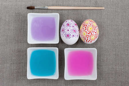 Painting Easter eggs, colored water and paintbrush photo