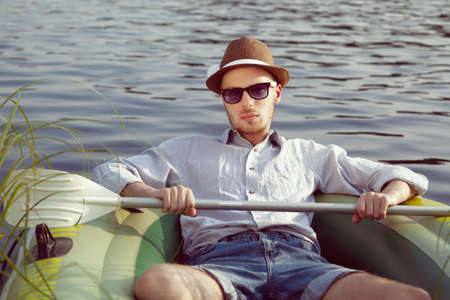 Young handsome man resting in a boat on the lake, sunny summer day photo