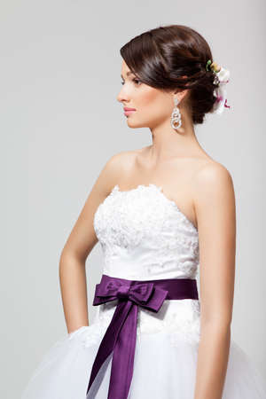 Portrait of a beautiful brunette bride with orhid in hairdo and white wedding dress, in studio photo