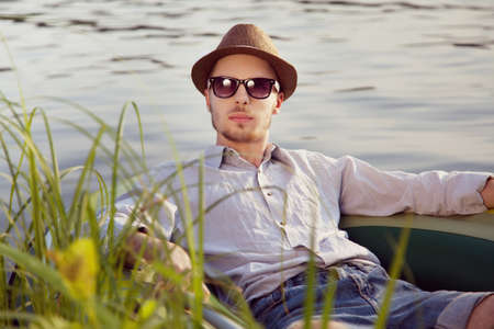 Portrait of a young handsome man resting in a boat on the lake, sunny summer day photo