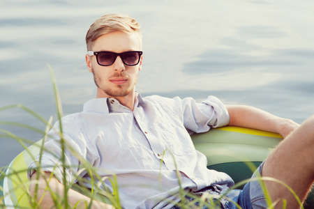 Portrait of a young handsome man resting in a boat on the lake, looking at camera, sunny summer day photo