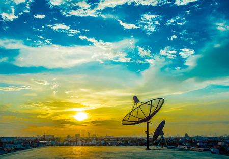 piatti satelite con il tramonto e lo sfondo della città Archivio Fotografico