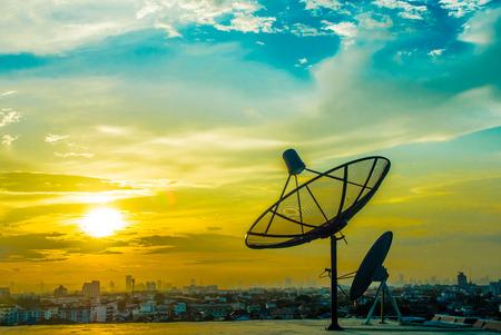 satelite: platos satelitales con puesta del sol y el fondo de la ciudad Foto de archivo