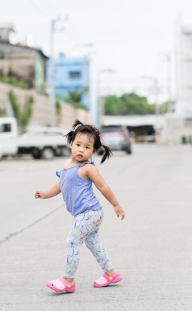 little girl walking on the road in car park