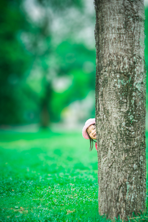 little girl sneaking behind the tree in the forest