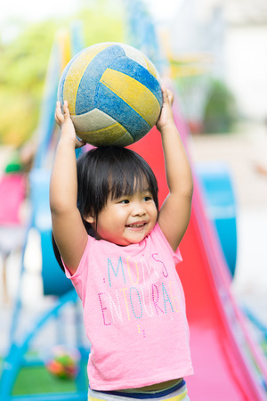 Asian little girl enjoys playing ball in a children playground