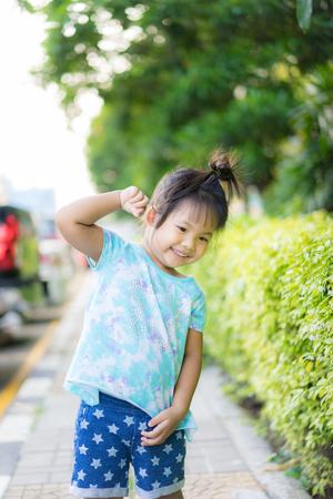 portrait of happy little girl standing ing in the park Banco de Imagens