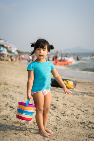 little girl holding a bucket for playing sand on the beach