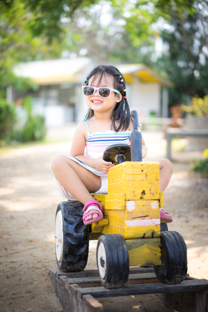 Cute asian little girl wear sunglasses playing by driving a old tractor in farm
