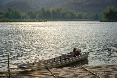 boats docked on a mountain lake with sunlight.Natural dam lake in forest. Imagens