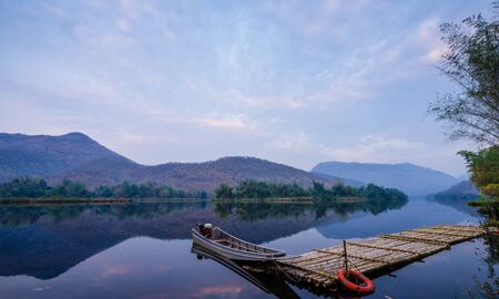 boats docked on a mountain lake and reflection.Natural dam lake in forest. Archivio Fotografico