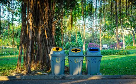 Three trashcans in a park with green tree and plants background in public park 版權商用圖片