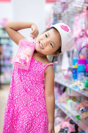 little girl show doll while shopping in mall Foto de archivo - 129912813