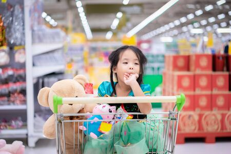 little asian girl in princess costume sitting with dolls in the cart between shopping Foto de archivo - 129912829