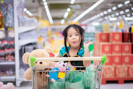 little asian girl in princess costume sitting with dolls in the cart between shopping Foto de archivo - 129912830