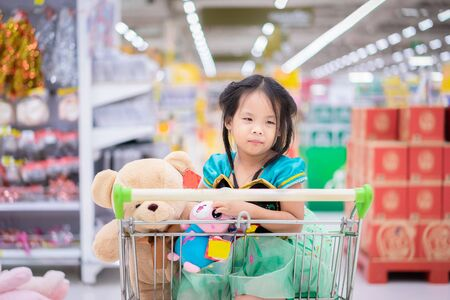 little asian girl in princess costume sitting with dolls in the cart between shopping Foto de archivo - 129912832