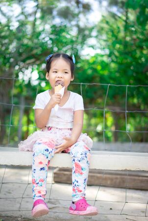 Asian little girl eating an ice cream outdoors with natural light blur background 스톡 콘텐츠