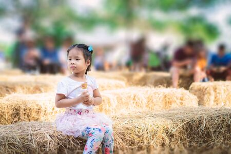 Asian little girl sitting on straw seat and eating an ice cream outdoors with people blur background