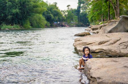 little girl eating near the river Stock Photo