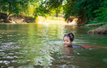niña asiática jugando en el río con la luz del sol