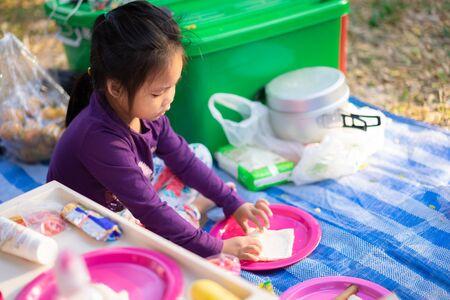 little girl making breakfast between camping