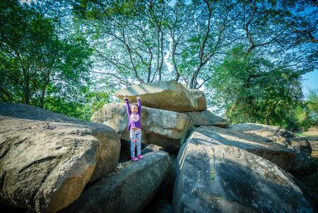 little girl standing with raised hands on rock and tree background Stok Fotoğraf