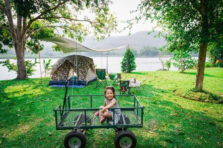 little girl sitting in wagon while going camping.The concept of outdoor activities and adventures in nature.