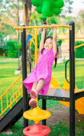 Cute asian little girl hanging on a horizontal bar while playing in the playground Foto de archivo