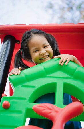 Asian little girl enjoys playing in a children playground Standard-Bild