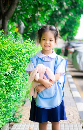 Portrait of happy little girl in Thai school uniform with doll standing in the park