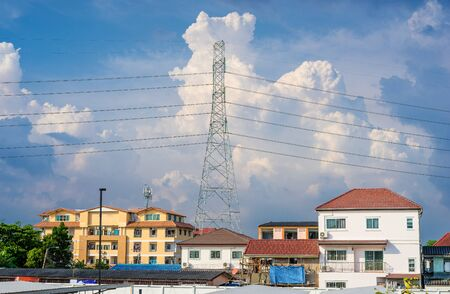 Background of electricity pole system with home in city with cloudy sky