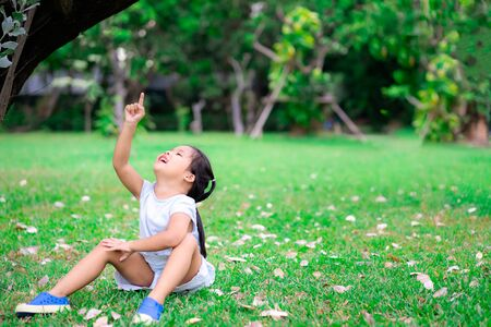 Cute little asian girl sitting on grass pointing to the sky