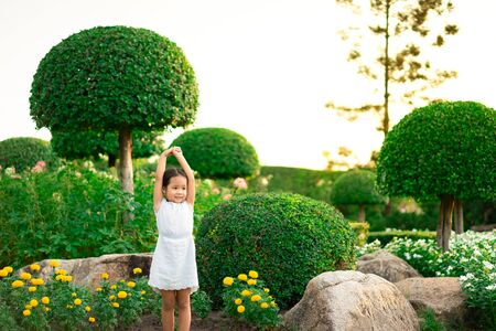 Happy cute little girl standing on the rock and open hands with the sunset in summer.Freedom concept. Stockfoto