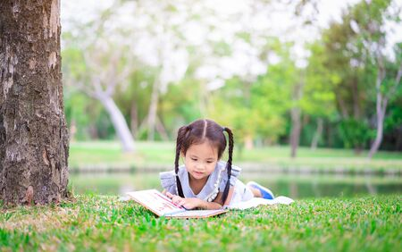 cute little girl  reading a book while lying in the park