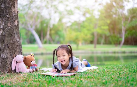 cute little girl  reading a book while lying with a doll in the park