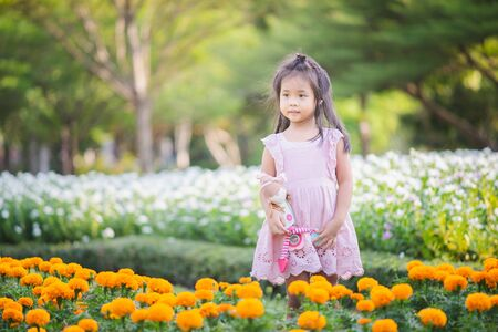 Cute little asian girl with a doll in the garden
